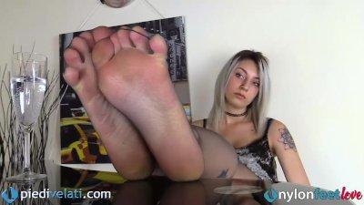 La bionda toglie i tacchi e mostra i piedi in collant